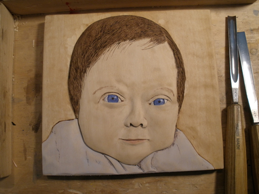 relief woodcarving of baby
